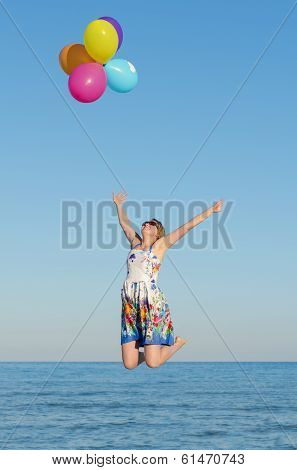 Young Woman With Colorful Balloons Over Sea.