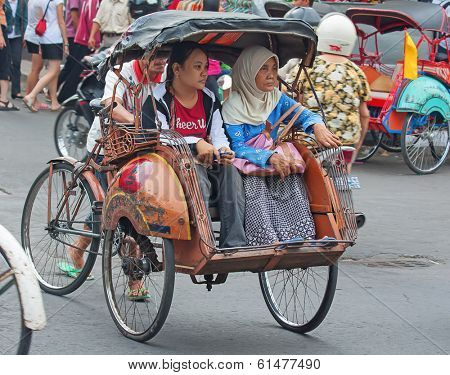 YOGYAKARTA, INDONESIA - AUGUST 03: Traditional rikshaw transport on streets of Yogyakarta, Java, Indonesia on August 03, 2010. Bicycle rikshaw remains popular means of transport in many Indonesian cities.
