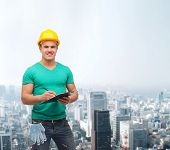 repair, construction and maintenance concept - smiling man in helmet with clipboard