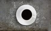 Conceptual image of cup of coffee with business sketches at background