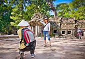 Beautiful young couple at Prasat Ta Prum or Ta Prohm Temple complex, near Siem Reap, Cambodia.