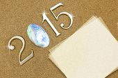 Year 2015 numbers with blank paper card on the sand