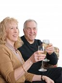 sitting Senior couple toasting someone with a glass of wine, isolated on white