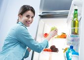 picture of refrigerator  - Young cheerful woman taking a green apple from refrigerator and smiling at camera - JPG