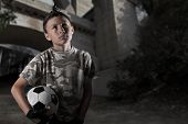 stock photo of underpass  - A young boy holding a soccer ball near an urban underpass  - JPG