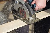 pic of sawing  - Closeup view of a man that is cutting wooden board electric circular saw - JPG