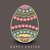 Happy Easter celebration card with colorful floral design decorated egg on brown background.