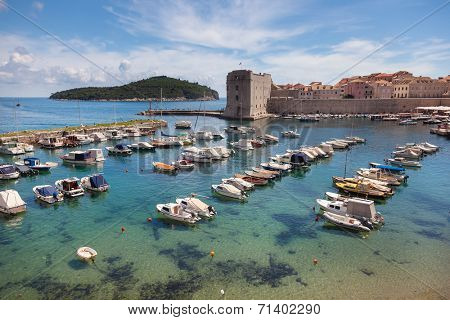 DUBROVNIK, CROATIA - MAY 28, 2014: Small boats in city port with Lokrum island and St. John fortress in background. Port is safe haven for many private boats of local citizens.