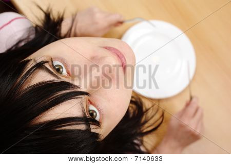 Beautiful Girl With By Empty Plate At The Table
