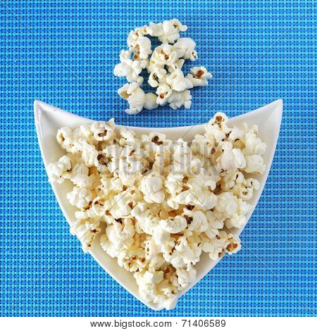 a bowl of appetizing popcorn on a blue tablecloth