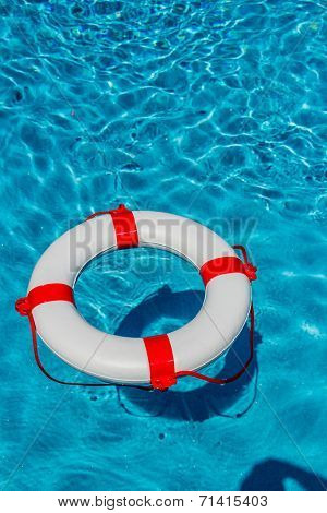 an emergency tire floating in a swimming pool. symbol photo for rescue and crisis management in the financial crisis and banking crisis.