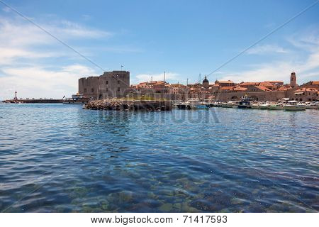 Small boats in city port with St. John fortress in background. Port is safe haven for many private boats of local citizens.