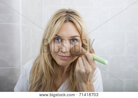 Portrait of young woman applying blush in bathroom