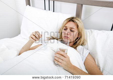 Woman suffering from cold holding water and tablet in bed