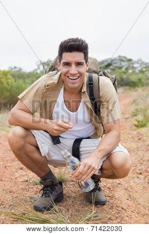 Portrait of a cheerful hiking man crouching on mountain terrain