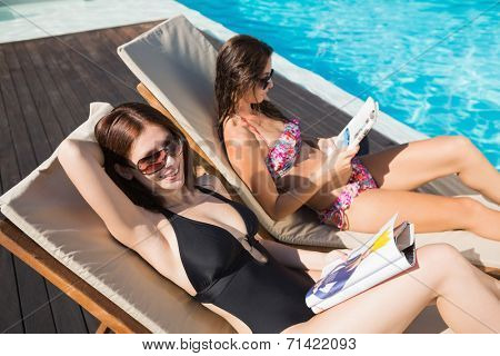 Side view of two young women reading books on sun loungers by swimming pool