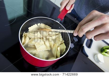 Midsection of man cooking pasta on stove in kitchen