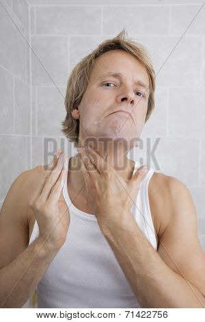 Portrait of mid-adult man applying aftershave moisturizer in bathroom