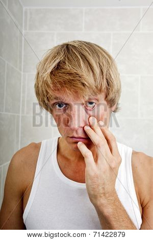 Portrait of sleepy man pulling eyelid in bathroom