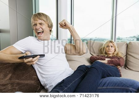 Angry woman staring at cheerful man as he watches TV in living room at home