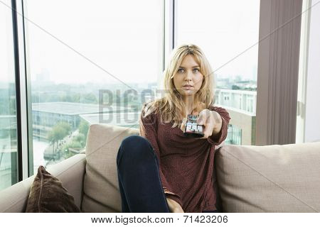 Portrait of blue eyed woman watching television on sofa at home