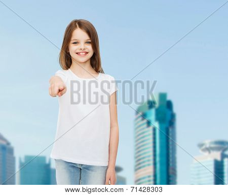 advertising, childhood, gesture and people concept - smiling girl in white t-shirt pointing finger on you over business center background