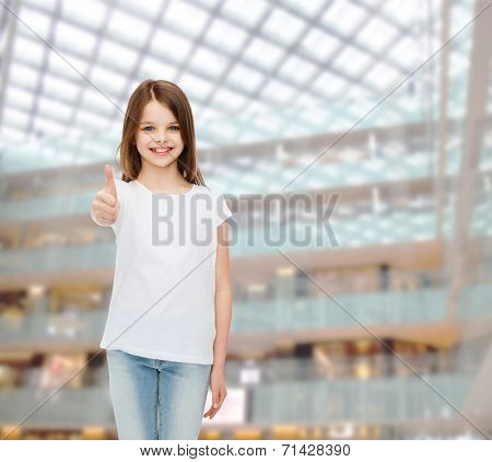 advertising, childhood, gesture, consumerism and people - smiling girl in white t-shirt showing thumbs up over shopping center background