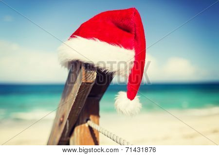 beach, summer, vacations, christmas and sea concept - close up of santa helper hat on beach