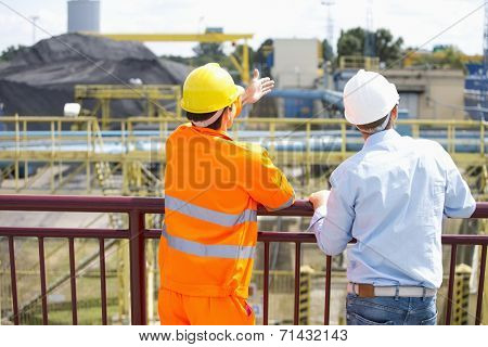 Back view of architects inspecting construction site