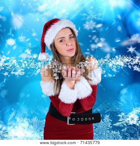 Sexy santa girl blowing over hands against blue snow flake pattern design