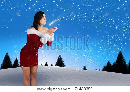 Pretty girl in santa outfit blowing against snow falling on fir tree forest