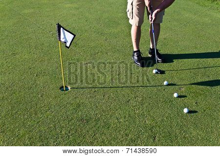Golfer Practicing Putting With Several Golf Balls