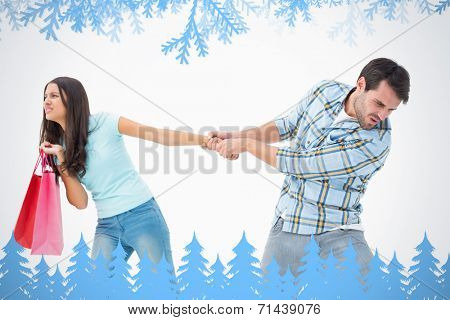 Attractive young man pulling his shopaholic girlfriend against frost and fir trees in blue