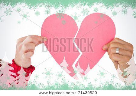 Couple holding two halves of broken heart against green snowflake design