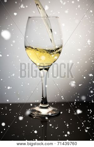 Snow falling against white wine being poured into clear wine glass