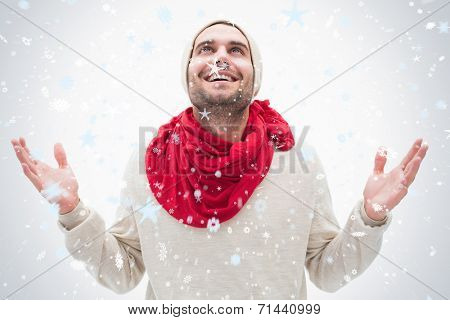Attractive young man in warm clothes with hands up against snow falling
