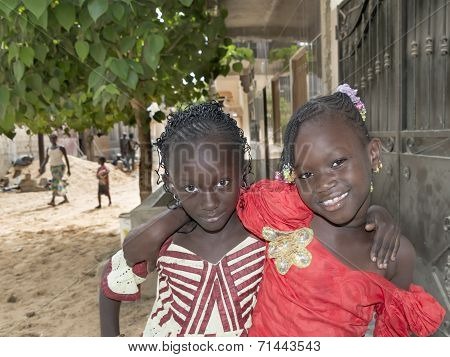 Two unidentified girls in the street wearing traditional dresses