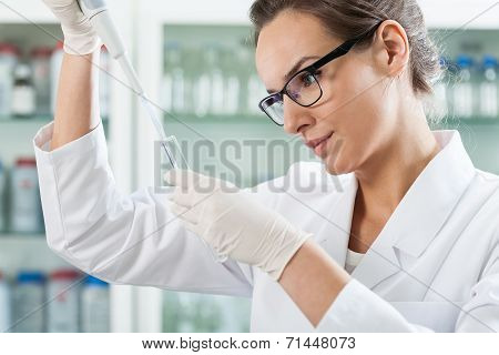 Scientist Using Pipette In Laboratory