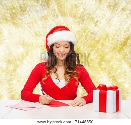christmas, holidays, celebration, greeting and people concept - smiling woman in santa helper hat with gift box writing letter or sending post card over yellow lights background