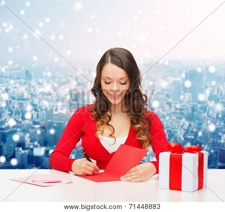 christmas, holidays, celebration, greeting and people concept - smiling woman with gift box writing letter or sending post card over snowy city background