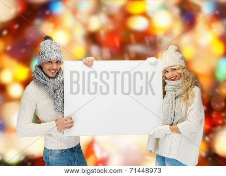 happiness, winter holidays, christmas, advertising and people concept - smiling couple in winter clothes holding big white blank board over shiny lights background