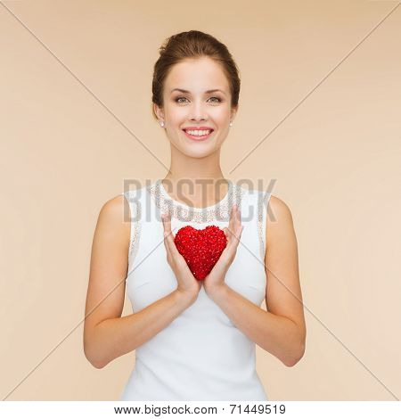 happiness, health, charity and love concept - smiling woman in white dress with red heart over beige background