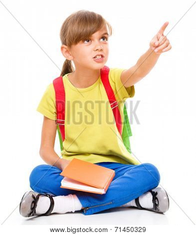 Portrait of a little girl with book, pointing up using her index finger, isolated over white