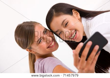 Two Smiling Young Women Taking Self Portrait With Cell Phone