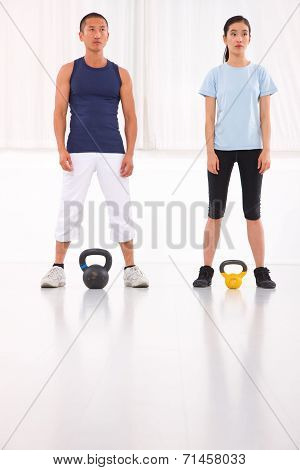 Asian Man And Woman Doing Kettle Bell Crossfit Exercise