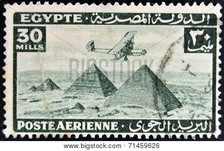 EGYPT - CIRCA 1946: stamp printed in Egypt shows plane over Pyramids at Giza circa 1946