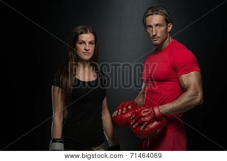 Fit Woman And Her Trainer Boxing Indoors