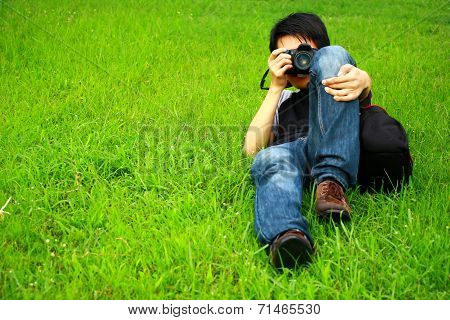 Photographer or cameraman prostrate on green grass self-portrait by two camera