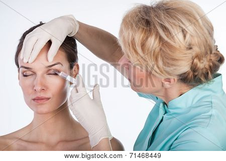 Doctor Injecting In The Forehead