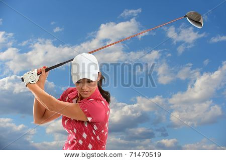 Female golfer swinging golf driver during sunny day